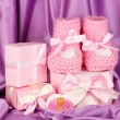 Pink baby boots, pacifier, gifts on silk background — Foto Stock