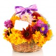Beautiful bouquet of bright flowers in basket with paper note isolated on w — Zdjęcie stockowe