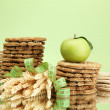 Tasty crispbread, apple, measuring tape and ears, on green background - Stock Photo