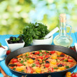 Colorful composition of delicious pizza, vegetables and spices on blue wood - Stock Photo