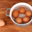 Boiled eggs in saucepan on wooden background — Stock Photo #13848016