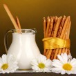 Tasty crispy sticks with pitcher with sour cream on wooden table on yellow — Stock Photo