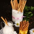 Tasty crispy sticks with pitcher and glass with sour cream on wooden table — Stock Photo #13848114