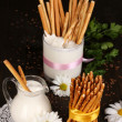 Tasty crispy sticks with pitcher and glass with sour cream on wooden table — Stock Photo