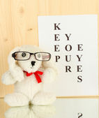 Eyesight test chart with glasses and with toy on wooden background close-up — Stock Photo