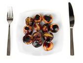 Roasted chestnuts in the white plate with fork and knife isolated on white — Stock Photo
