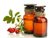 Medicine bottles with hip roses, isolated on white — Stock Photo