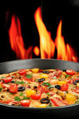 Delicious pizza with seafood on fire background — Stock Photo
