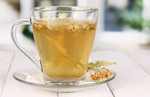 Glass cup of tea with linden on wooden table on window background — Stock Photo