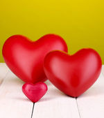 Decorative red hearts on white wooden table on green background — Stock Photo