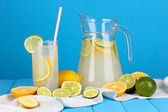 Citrus lemonade in pitcher and glass of citrus around on wooden table on bl — Stock Photo