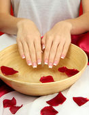 Woman hands with wooden bowl of water with petals, on red background — Stock Photo