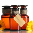 Medicine bottles and beautiful calendula flowers, isolated on white — Stock Photo