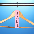 Wooden clothes hanger as sale symbol on blue background — Stock Photo #13852020