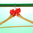 Royalty-Free Stock Photo: Beautiful red bow hanging on wooden hanger on green background