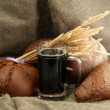 Tankard of kvass and rye breads with ears, on burlap background — Stock Photo #13852263