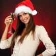 Beautiful young woman with glass of champagne, on red background — Stock Photo #13853658