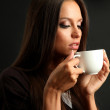 Beautiful young woman with cup of coffee, on brown background — Stock Photo #13853661