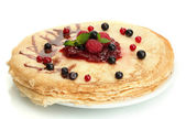 Delicious pancakes with berries and jam on plate isolated on white — Stock Photo