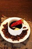Kawa i pieprz na drewnianym stole na brązowym tle — Zdjęcie stockowe