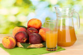 Ripe peaches and juice on wooden table on natural background — Stock Photo