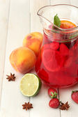 Sangria in jar with fruits, on white wooden table — Stock Photo