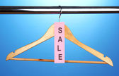 Wooden clothes hanger as sale symbol on blue background — Stock Photo