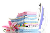 Pile of clothes with lily and electric iron, isolated on white — Stock Photo