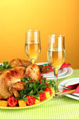 Banquet table with roast chicken on orange background close-up — Stock Photo