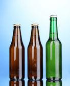 Mavi zemin üzerine bira şişesi — Stok fotoğraf
