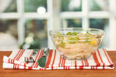 Salad of squid rings, lemon and lettuce in a glass bowl on wooden table — Stock Photo