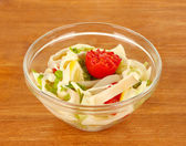 Squid salad with vegetables in a glass bowl on wooden background close-up — Stock Photo