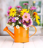 Beautiful bouquet of bright flowers in watering can on wooden table — Stock Photo
