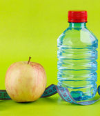 Bottle of water, apple and measuring tape on green background — Stock Photo