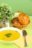 Fragrant soup in white plate on green tablecloth on green background close- — Stock Photo