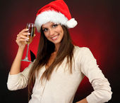 Beautiful young woman with glass of champagne, on red background — Stock Photo