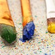 Brushes with colorful paint on colorful splashes background close-up — Stockfoto