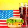 Tasty sandwich and cola with american flag, on yellow background — Lizenzfreies Foto