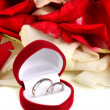 Royalty-Free Stock Photo: Beautiful box with wedding rings on red, white and pink rose petals