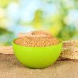 Arnautka in green bowl with spikelets on green background close-up - Stock Photo
