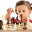 Beautiful little girl and chess isolated on white — Stock Photo