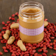 Delicious peanut butter in jar on wooden table close-up - Stock Photo