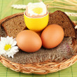 Boiled eggs on wicker matt on color background — Stock Photo