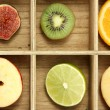 Sliced fruits in wooden box background - Stock Photo