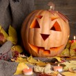 Halloween pumpkin and autumn leaves, on wooden background — Stock Photo #13871031