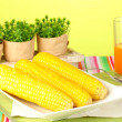 Boiled corn and juice on a green background — Photo