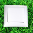 Modern light switch on green grass — Stock Photo