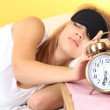 Young beautiful woman lying on bed with eye mask and alarm clock, on yellow background — Stock Photo