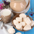 Pitcher and cup of milk with meringues on wooden table close-up — Stock Photo