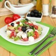 Fresh greek salad on plate on wooden table close-up — Stock Photo